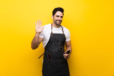 Young hairdresser man over isolated yellow background saluting with hand with happy expression