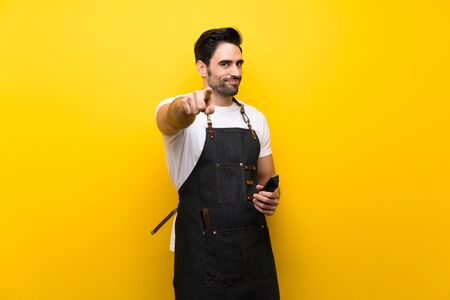 Young hairdresser man over isolated yellow background points finger at you with a confident expression Фото со стока