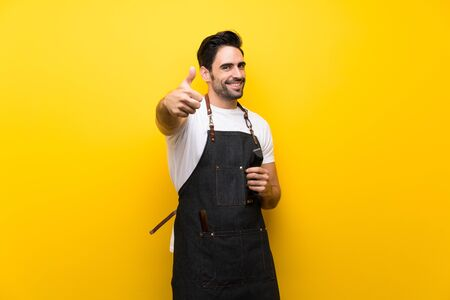 Young hairdresser man over isolated yellow background with thumbs up because something good has happened