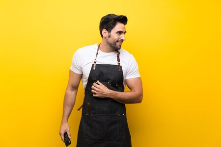 Young hairdresser man over isolated yellow background