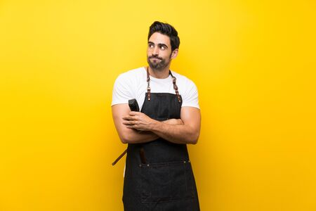 Young hairdresser man over isolated yellow background making doubts gesture while lifting the shoulders