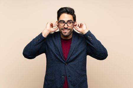 Handsome young man over isolated background frustrated and covering ears Stock Photo