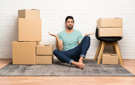 Handsome young man moving in new home among boxes having doubts with confuse face expression Фото со стока