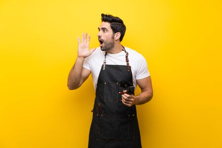 Young hairdresser man over isolated yellow background shouting with mouth wide open