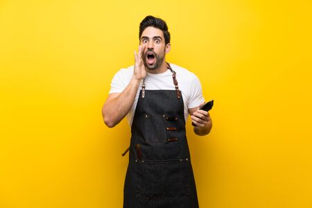 Young hairdresser man over isolated yellow background with surprise and shocked facial expression