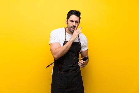 Young hairdresser man over isolated yellow background whispering something