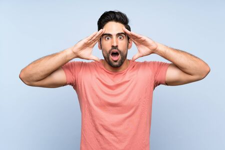 Handsome young man in pink shirt over isolated blue background with surprise expression