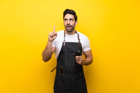 Young hairdresser man over isolated yellow background intending to realizes the solution while lifting a finger up