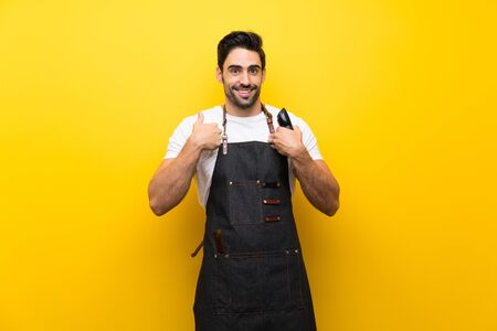 Young hairdresser man over isolated yellow background with surprise facial expression