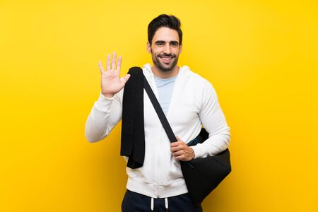 Young sport man over isolated yellow wall saluting with hand with happy expression Reklamní fotografie