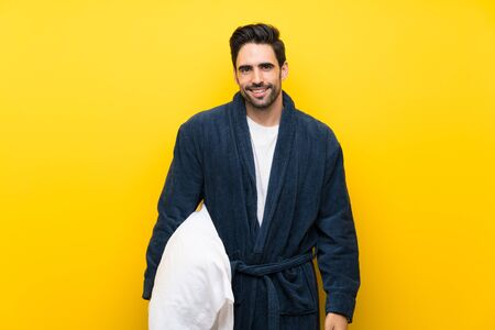 Handsome man in pajamas over isolated yellow wall