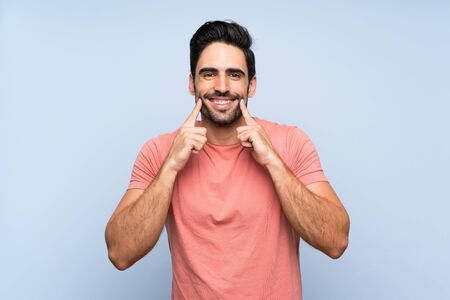 Handsome young man in pink shirt over isolated blue background smiling with a happy and pleasant expression Stok Fotoğraf