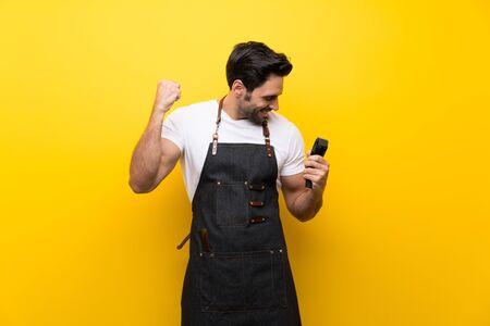 Young hairdresser man over isolated yellow background celebrating a victory