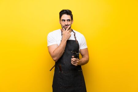 Young hairdresser man over isolated yellow background thinking an idea