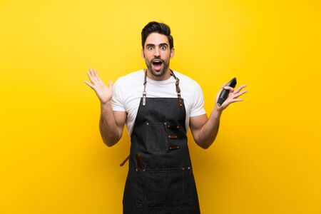 Young hairdresser man over isolated yellow background with shocked facial expression