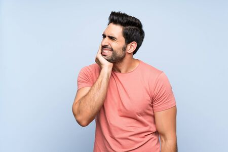 Handsome young man in pink shirt over isolated blue background with toothache