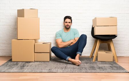 Handsome young man moving in new home among boxes keeping arms crossed Stok Fotoğraf