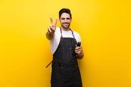 Young hairdresser man over isolated yellow background smiling and showing victory sign