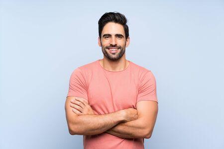 頭前の位置に腕を交差させ続ける孤立した青い背景の上にピンクのシャツを着たハンサムな若者