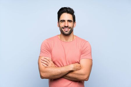 Beau jeune homme en chemise rose sur fond bleu isolé en gardant les bras croisés en position frontale