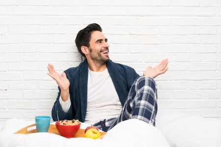 Man in bed with dressing gown and having breakfast with surprise facial expression