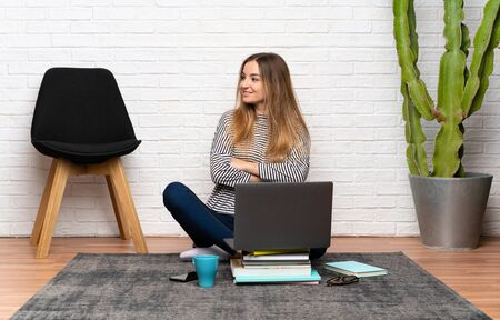 Young woman sitting on the floor with her laptop looking to the side