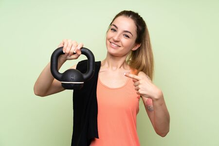 Young sport woman making weightliftingwith with a kettlebell Reklamní fotografie