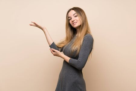 Young woman over isolated background extending hands to the side for inviting to come