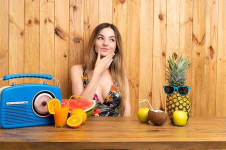 Young woman in swimsuit with lots of fruits thinking an idea 写真素材