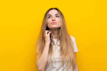 Young woman over isolated yellow wall thinking an idea 写真素材