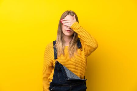 Woman with overalls over isolated yellow wall covering eyes by hands Stock Photo