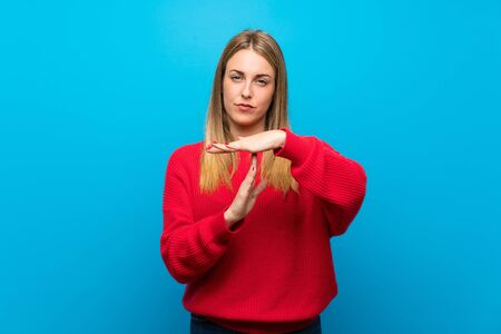 Woman with red sweater over blue wall making time out gesture