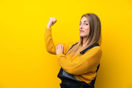 Woman with overalls over isolated yellow wall making strong gesture Standard-Bild