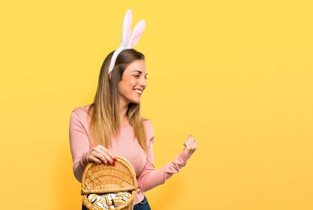 Young woman wearing bunny ears for Easter holidays celebrating a victory and happy for having won a prize on isolated yellow background