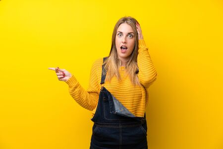 Woman with overalls over isolated yellow wall surprised and pointing finger to the side