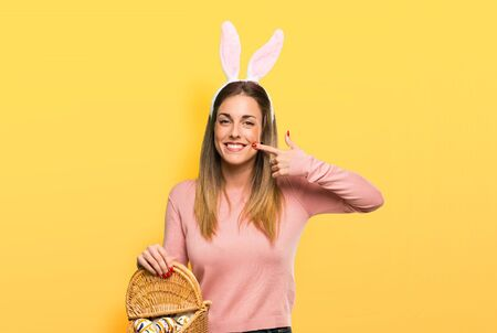 Young woman wearing bunny ears for Easter holidays smiling with a pleasant expression while pointing mouth with fingers on isolated yellow background