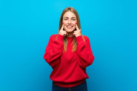 Woman with red sweater over blue wall smiling with a happy and pleasant expression