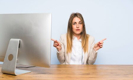 Young telemarketer woman pointing to the laterals having doubts