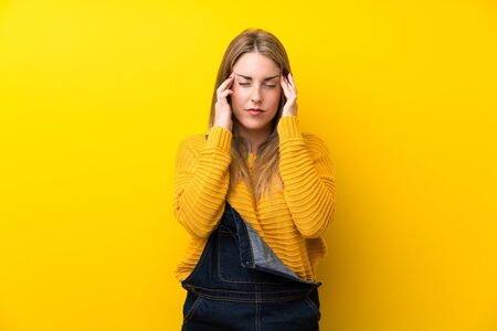 Woman with overalls over isolated yellow wall unhappy and frustrated with something. Negative facial expression