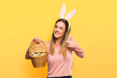 Young woman wearing bunny ears for Easter holidays giving a thumbs up gesture and smiling because has had success on isolated yellow background 版權商用圖片