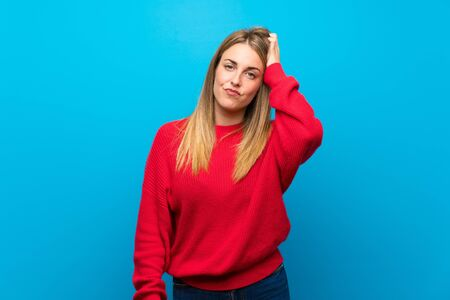 Woman with red sweater over blue wall with an expression of frustration and not understanding