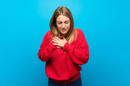 Woman with red sweater over blue wall having a pain in the heart Banco de Imagens