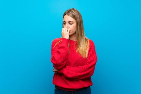 Woman with red sweater over blue wall having doubts