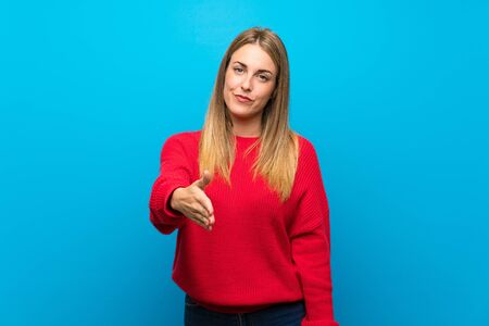 Woman with red sweater over blue wall shaking hands for closing a good deal