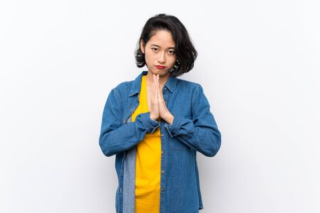 Asian young woman over isolated white background keeps palm together. Person asks for something