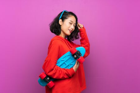Asian young girl with skate over purple background Stock fotó