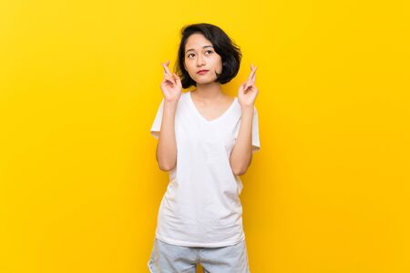 Asian young woman over isolated yellow wall with fingers crossing and wishing the best