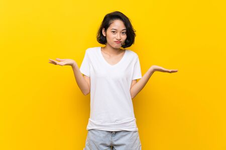 Asian young woman over isolated yellow wall having doubts while raising hands
