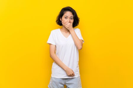 Asian young woman over isolated yellow wall covering mouth with hands Archivio Fotografico