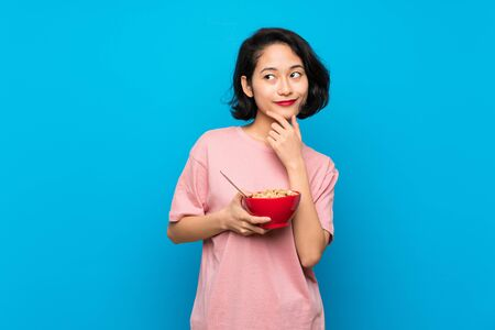 Asian young woman holding a bowl of cereals thinking an idea 写真素材